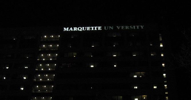 Marquette University Straz Tower sign mid-replacement. On the left is LED, on the right is the old neon lighting.