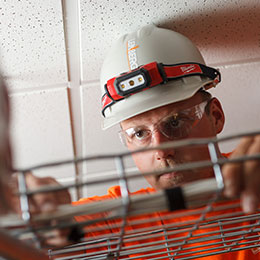IMG: data comm technician adjusting a cable rack