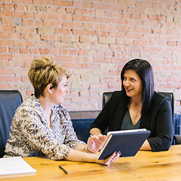 IMG: Two Business Women Talking at table