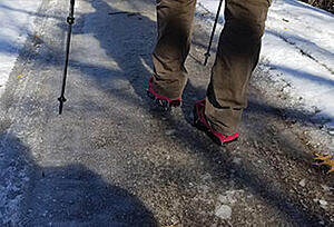 Hiker using Crampons to walk across ice covered trail in Wisconsin