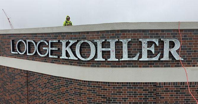 Lodge Kohler brand signage gets installed.