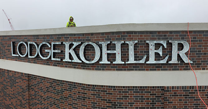 Lodge Kohler brand signage gets installed.